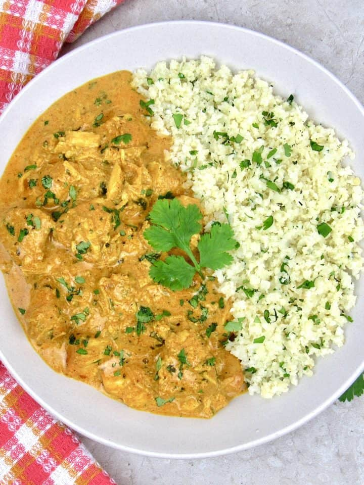 butter chicken on plate with cauliflower rice