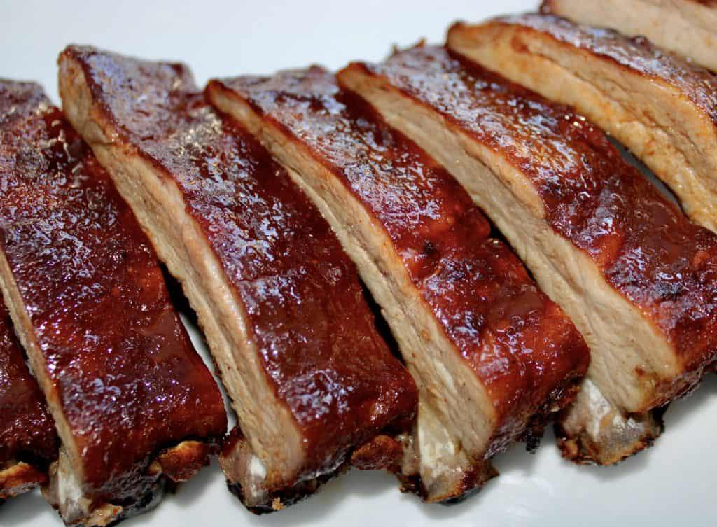 closeup of cut bbq ribs on baking sheet