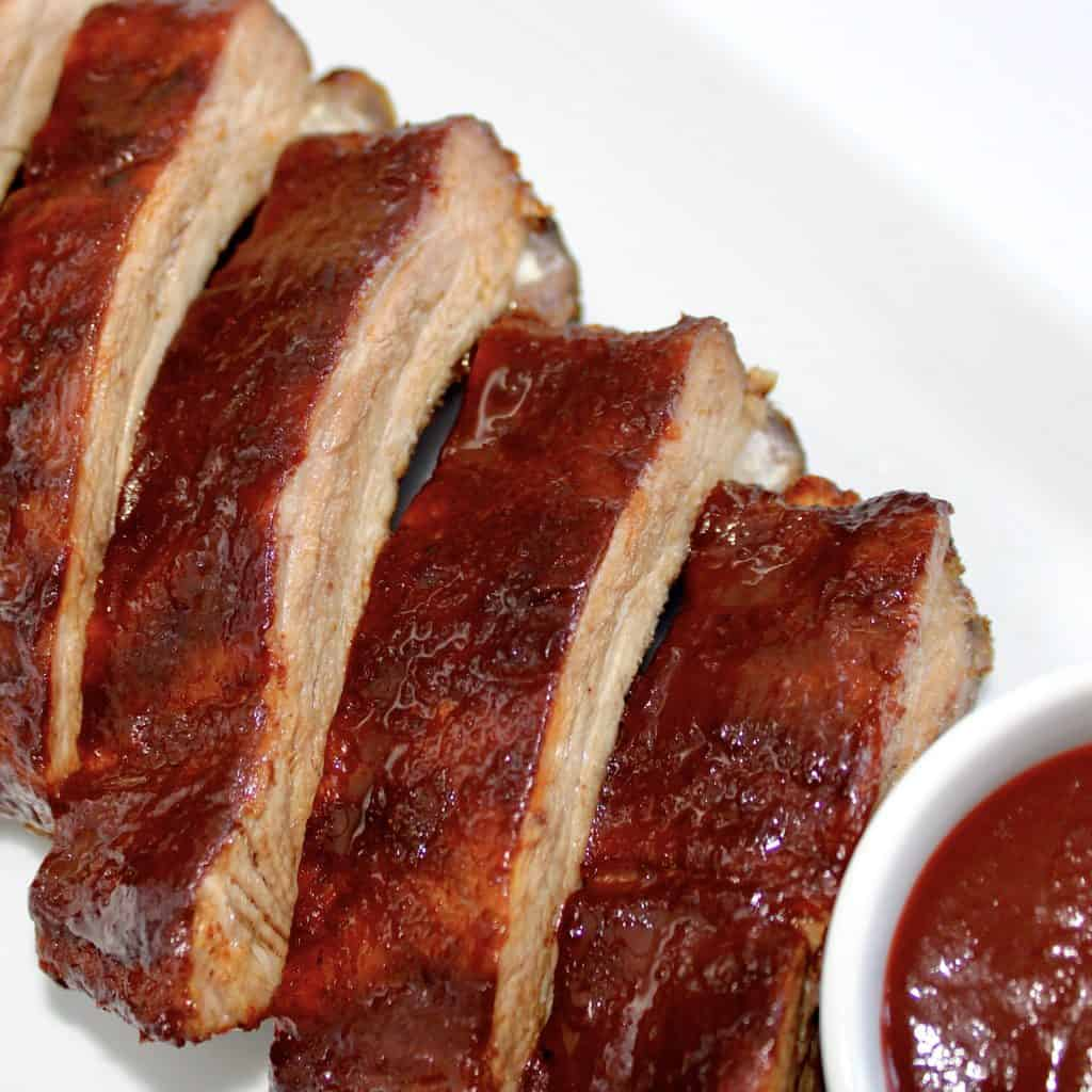4 bbq ribs on white plate with side of bbq sauce