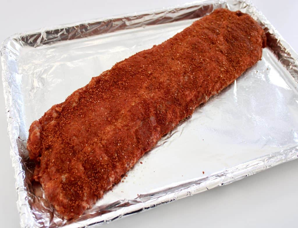 rack of ribs with dry rub on sheet pan