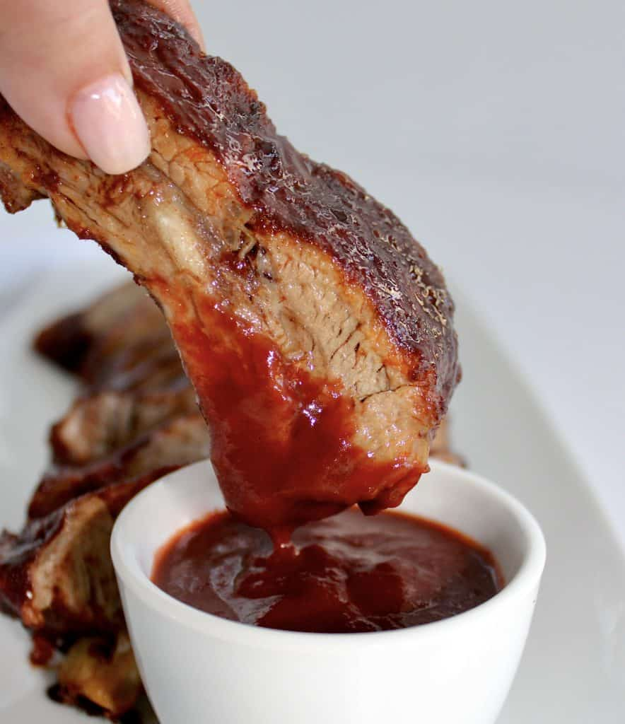 rib being dipped into bbq sauce