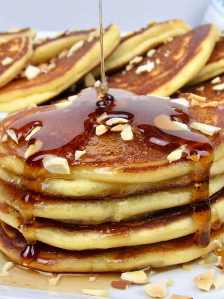 ricotta pancakes with syrup being poured over top