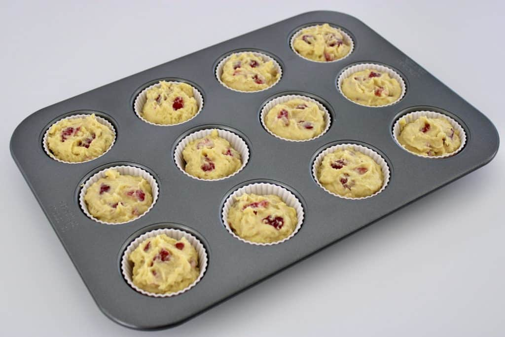Keto Strawberry Lemonade Muffins in a muffin pan with white liners