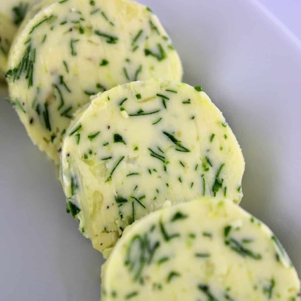 closeup of 3 discs of compound butter on white plate