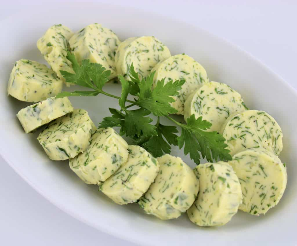 Garlic Herb Compound Butter arranged in a circle on white plate parsley in center