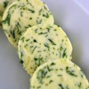 Garlic Herb Compound Butter in discs on white plate