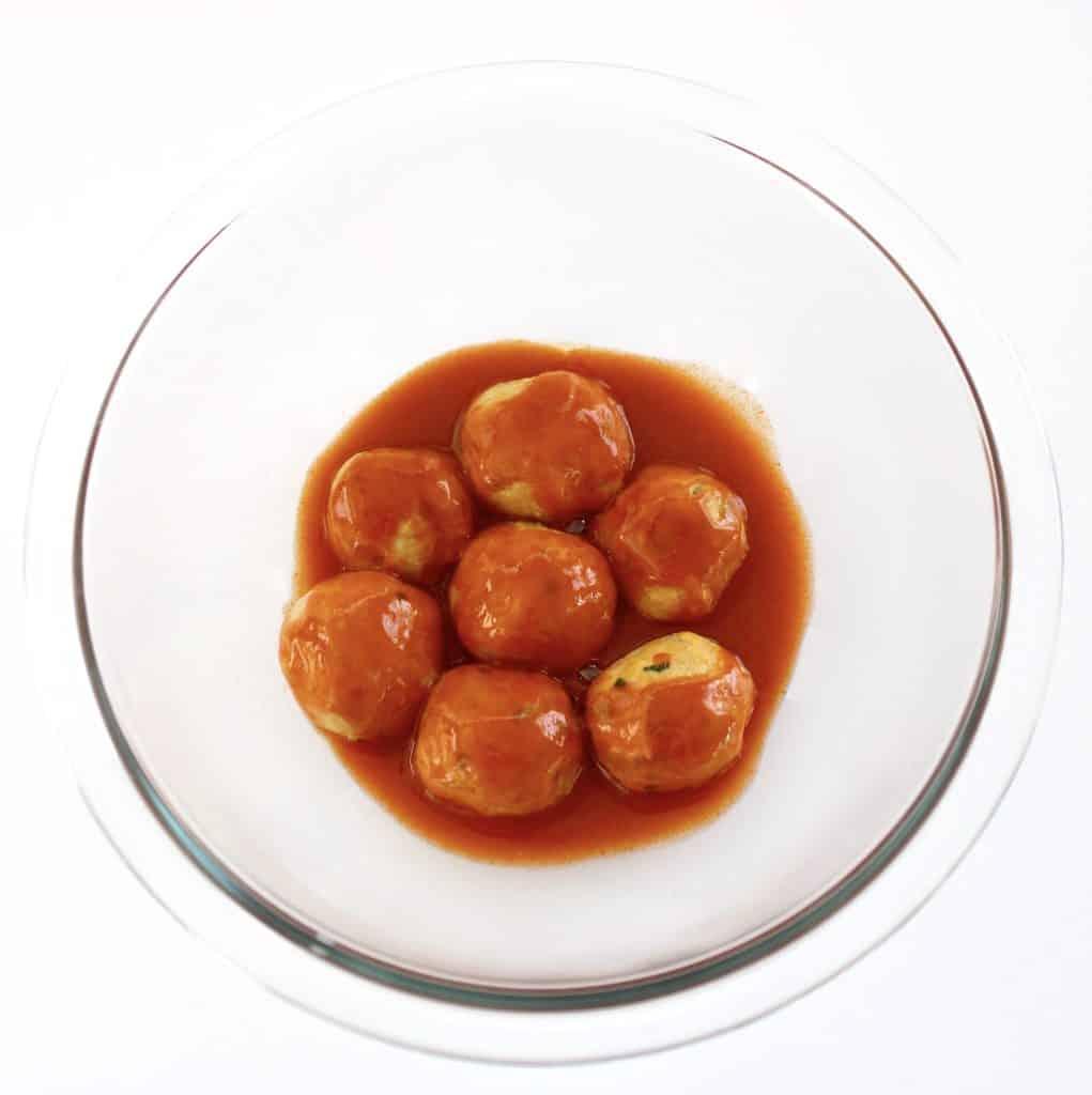 7 buffalo chicken meatballs in buffalo sauce in glass bowl