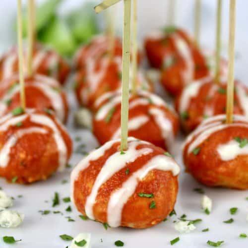Keto Buffalo Chicken Meatballs on white platter with fancy toothpicks