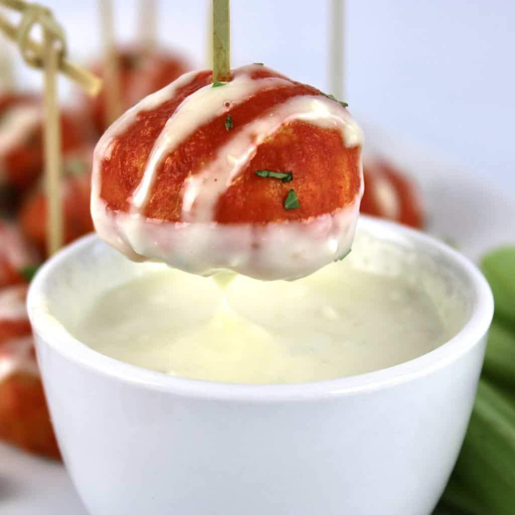 buffalo chicken meatball on toothpick being dipped into blue cheese dressing