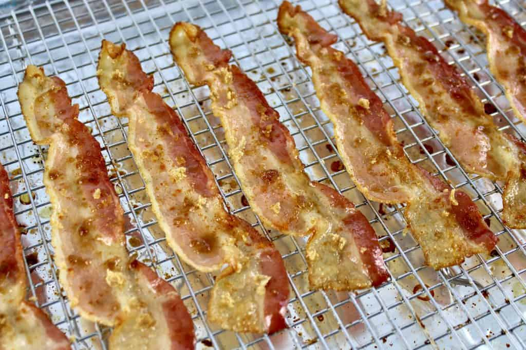 closeup of bacon on baking sheet with cayenne pepper and brown sugar sprinkled on top