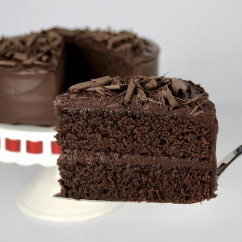 slice of Keto Chocolate Cake being held up with cake in background