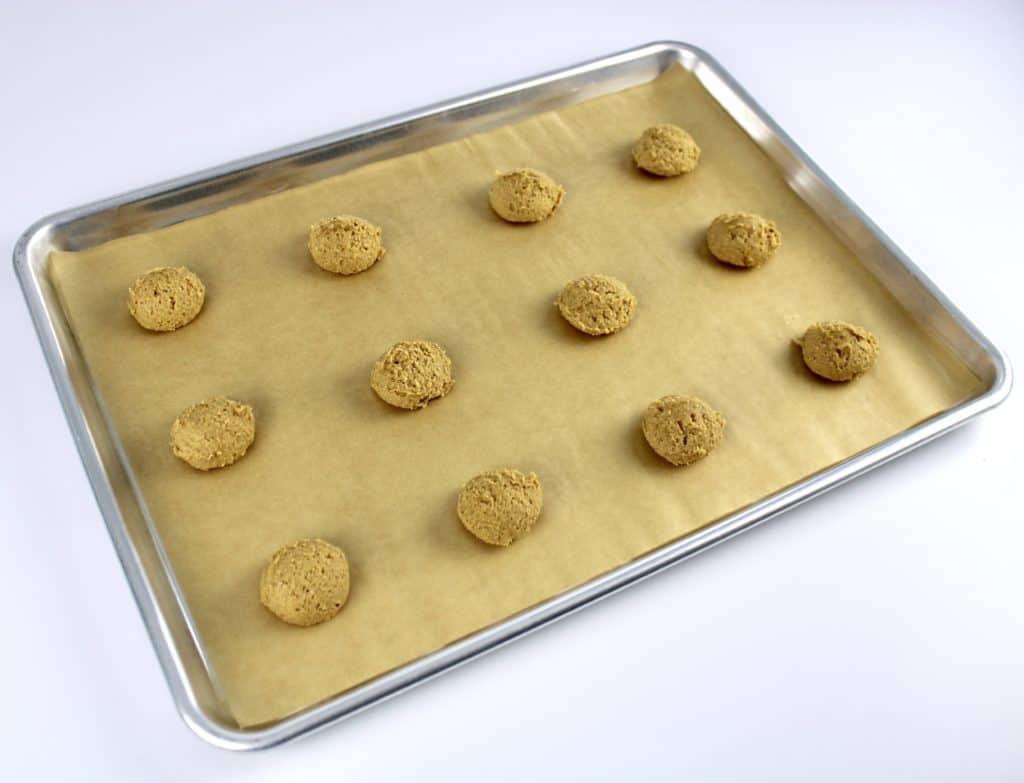 pumpkin cookie dough balls on baking sheet