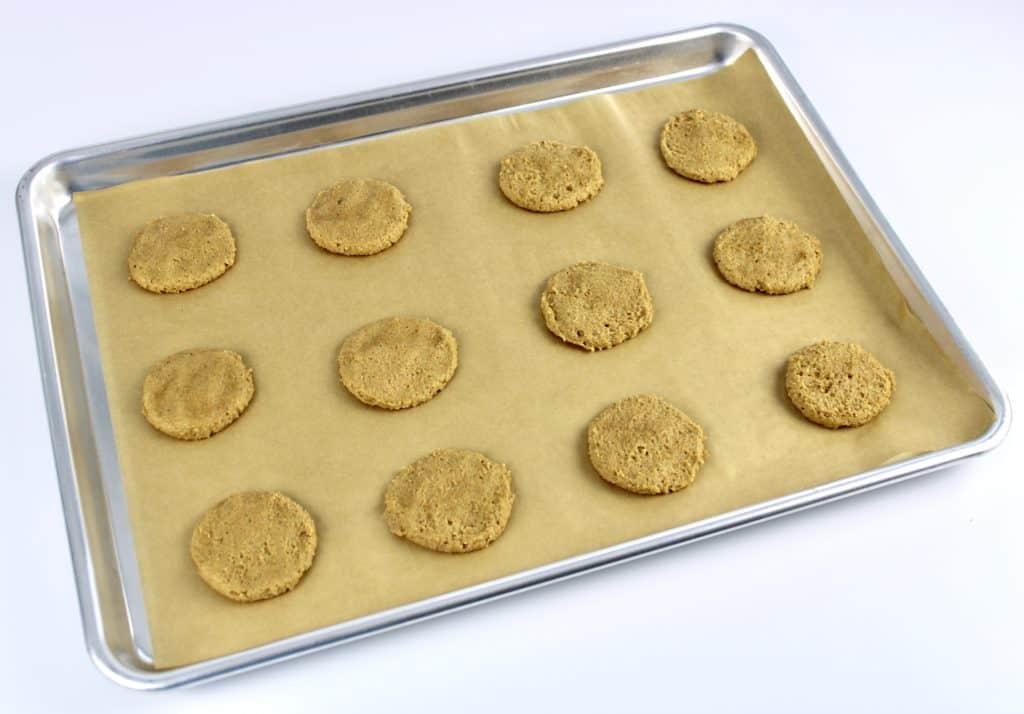 pumpkin cookie dough balls on baking sheet pressed down