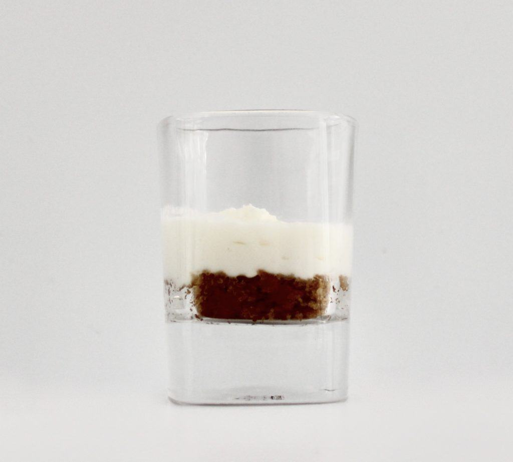 whip cream on top of crumbled cookie in shot glass