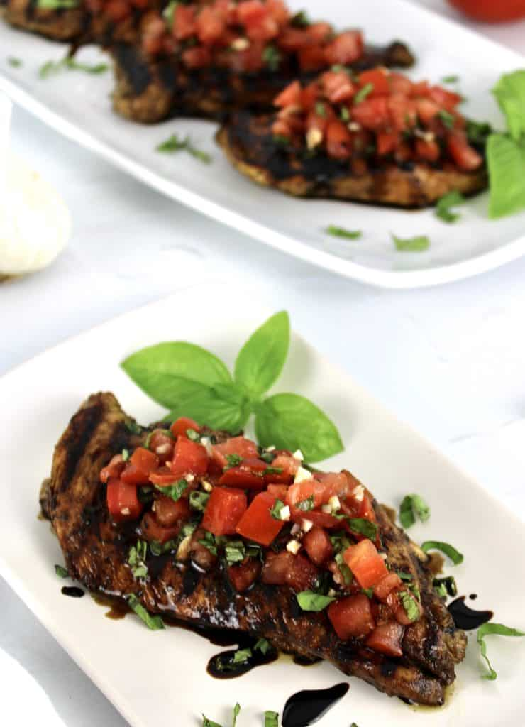 Grilled Bruschetta Chicken on white plate with platter in the background