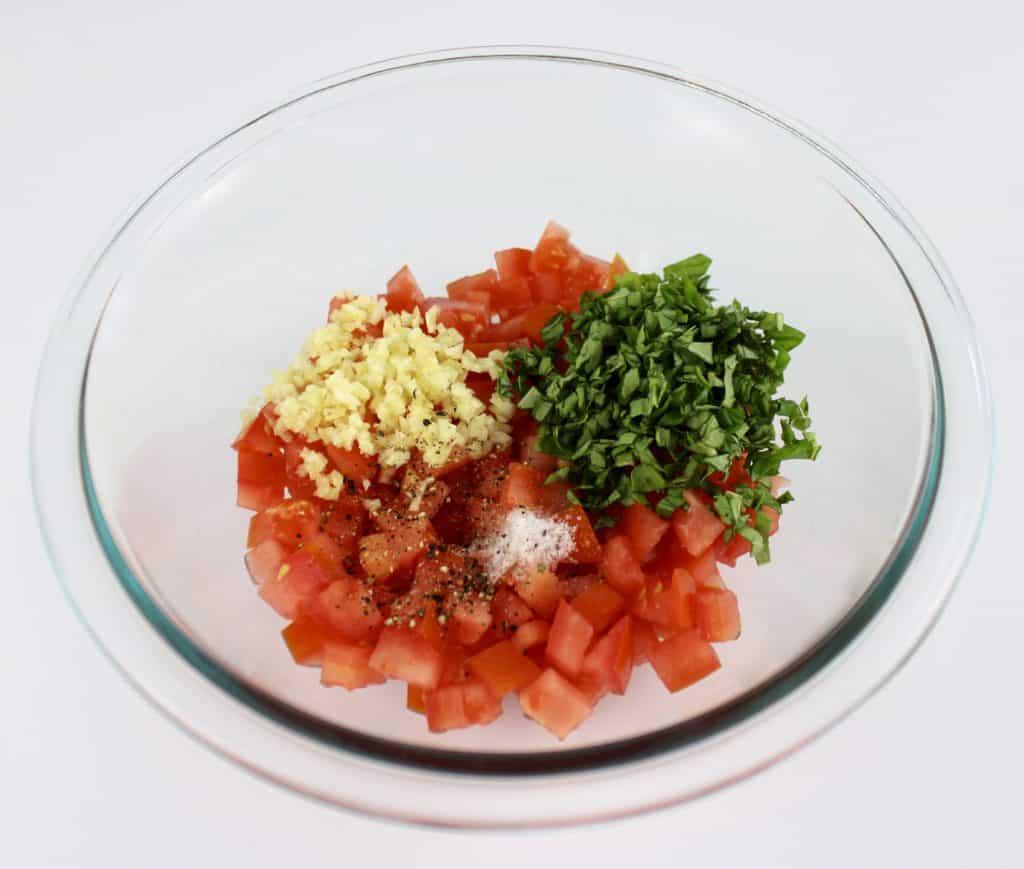bruschetta ingredients in glass bowl unmixed
