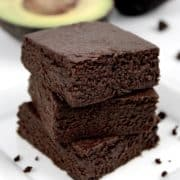 chocolate avocado brownies stacked up on white plate