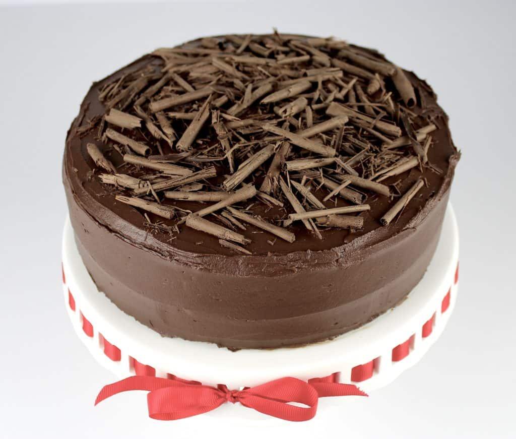 Keto Chocolate Cake on cake stand with chocolate shavings on top