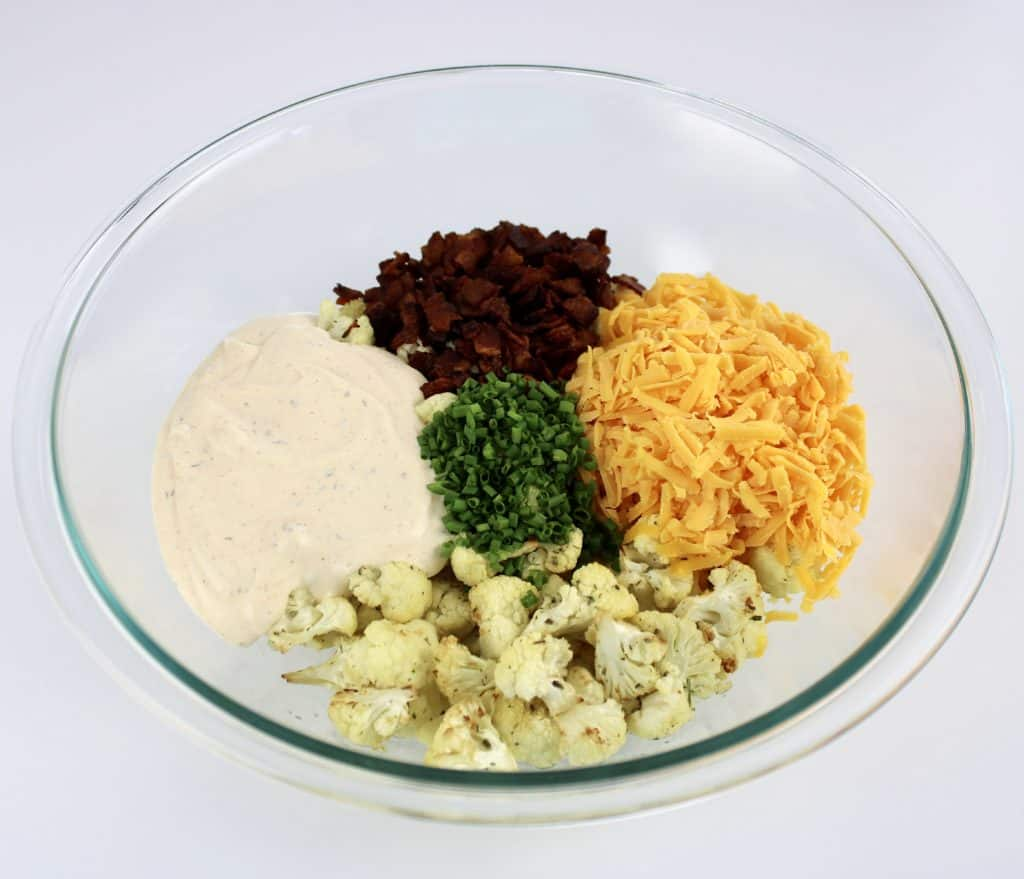 loaded cauliflower salad ingredients in glass bowl unmixed