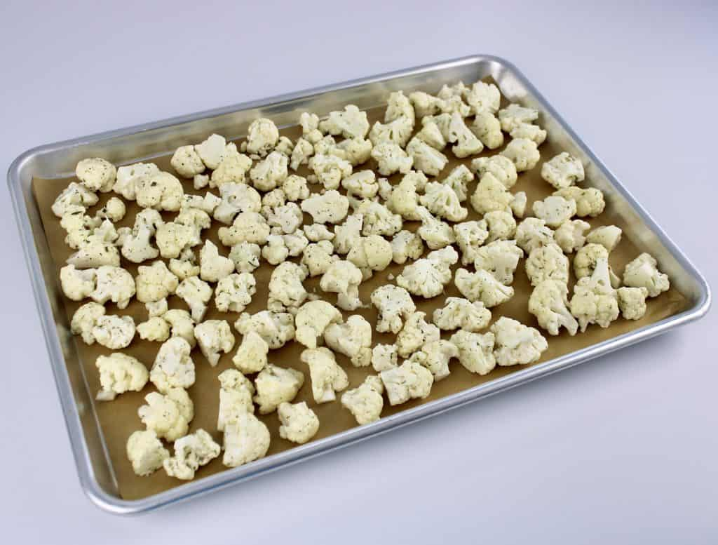 cauliflower florets with ranch seasoning over the top on parchment lined baking sheet