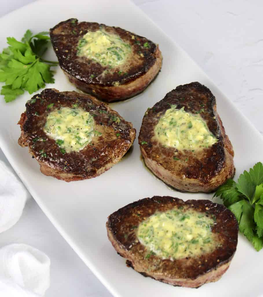 overhead view of 4 filet mignon steaks on white plate with compound butter on top