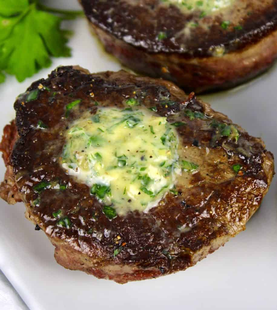 closeup overhead view of seared filet mignon with compound butter on top