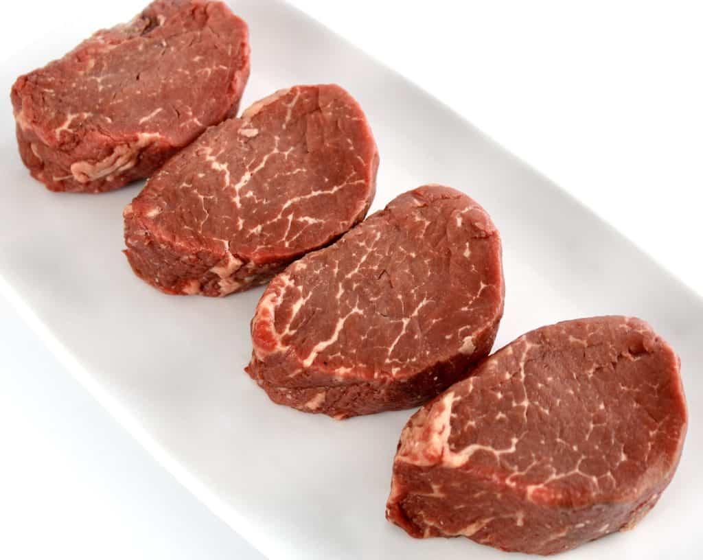 4 raw beef tenderloins on white plate