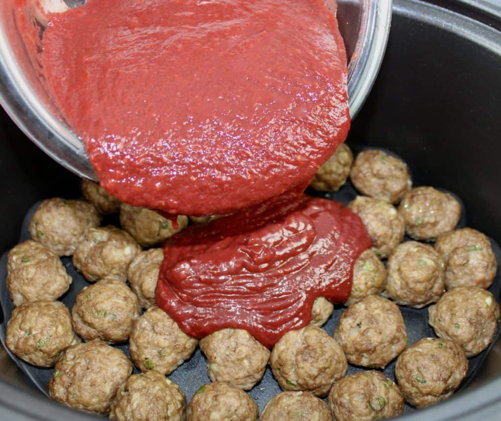 raspberry bbq sauce being poured over meatballs in crockpot