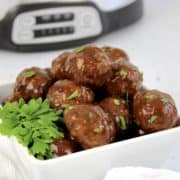 crockpot bbq meatballs in white bowl with crockpot in background
