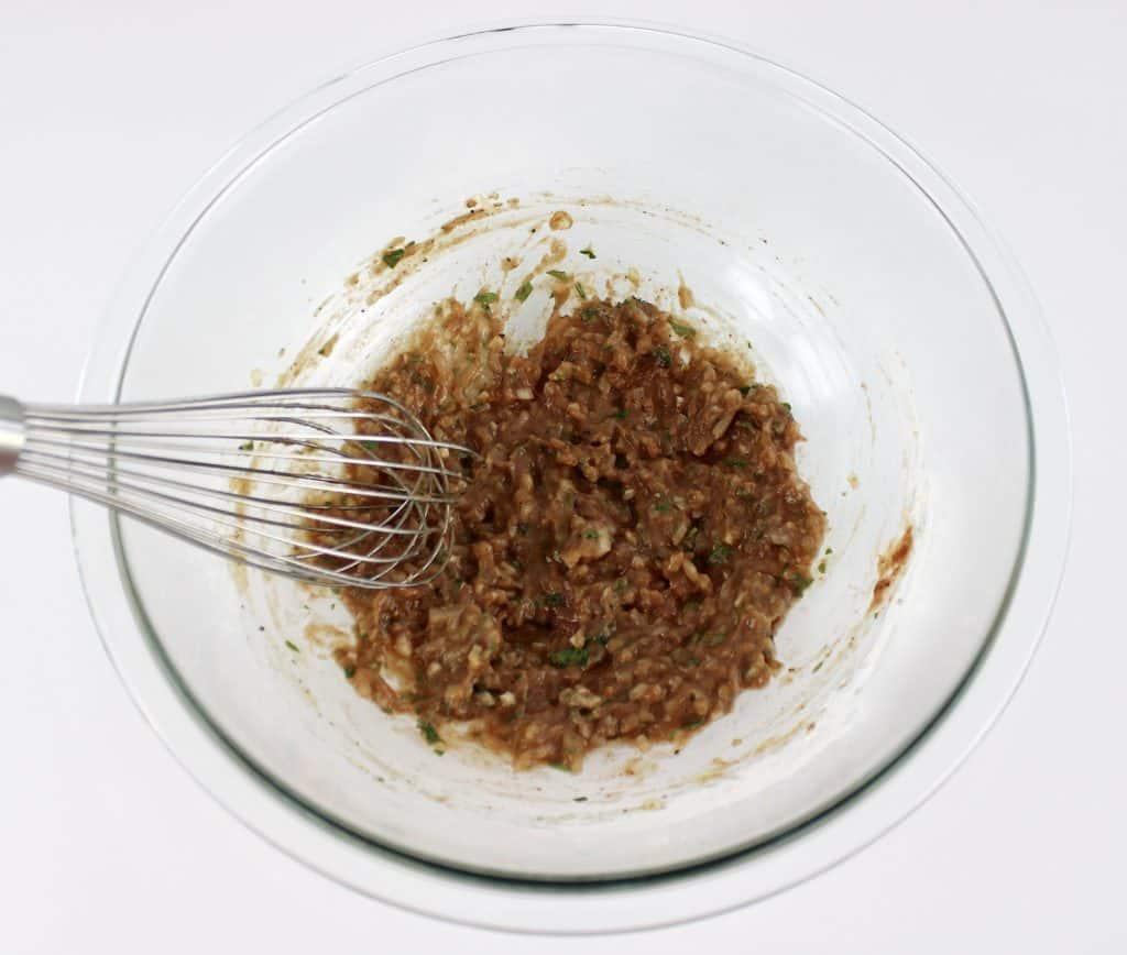crockpot bbq meatballs wet mixture in glass bowl mixed