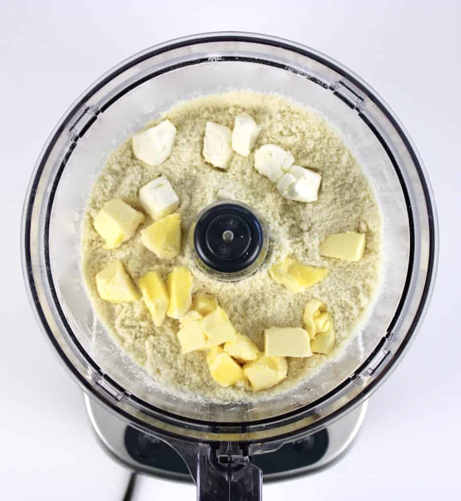 pie crust dry ingredients with butter and cream cheese cubes in food processor