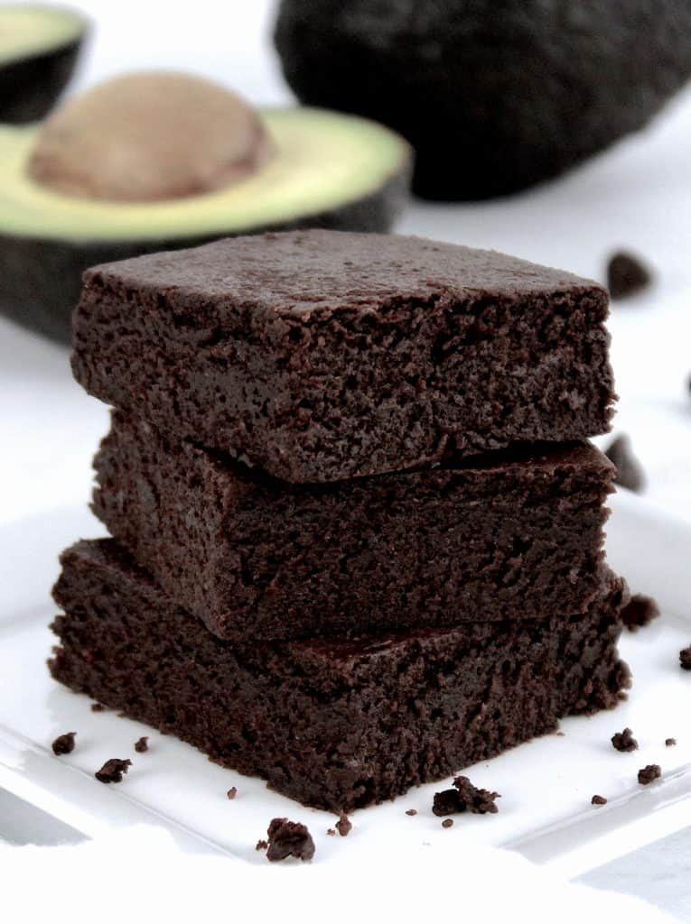 chocolate avocado brownies stacked up on white plate avocado in background