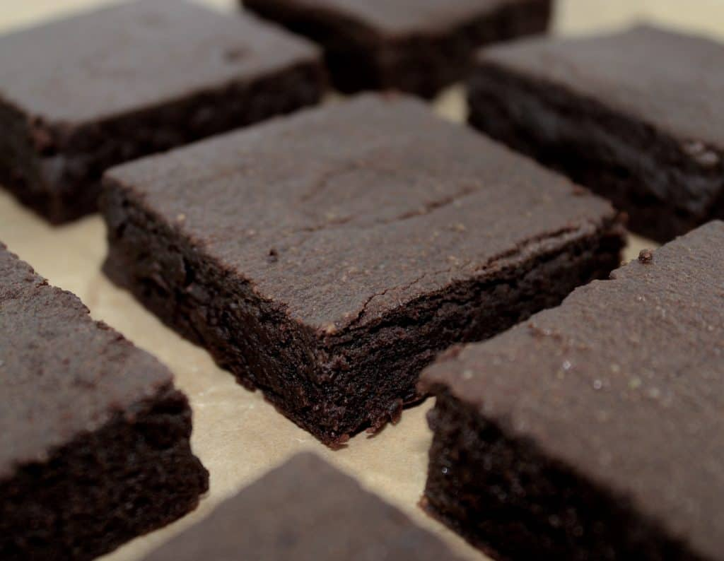 chocolate avocado brownies sliced on parchment paper