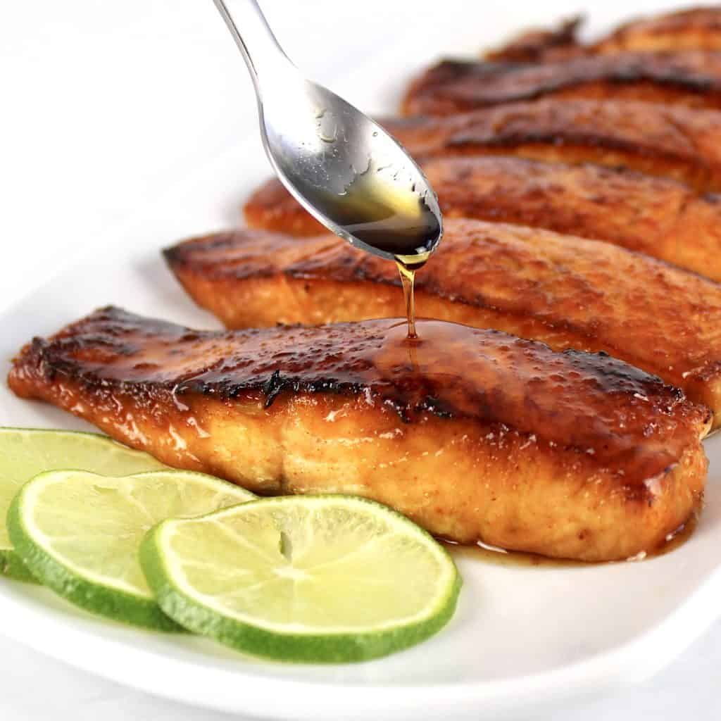 Maple Glazed Salmon on white plate with maple syrup being spooned over top