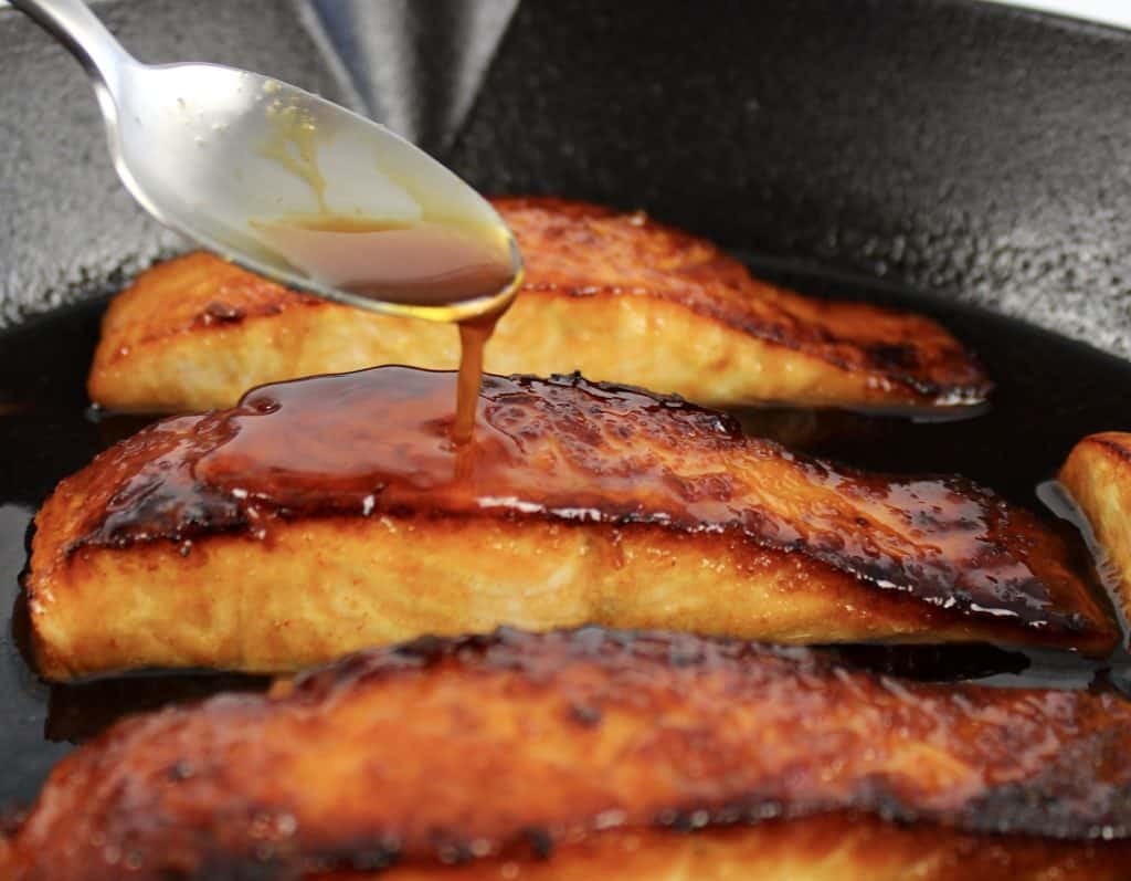 maple glaze being spooned over salmon in cast iron skillet