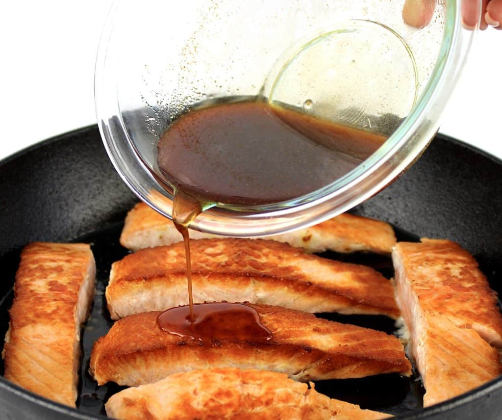 maple glaze being poured over salmon in skillet