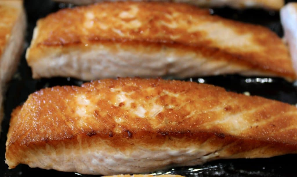 closeup of two pieces of seared salmon in cast iron skillet