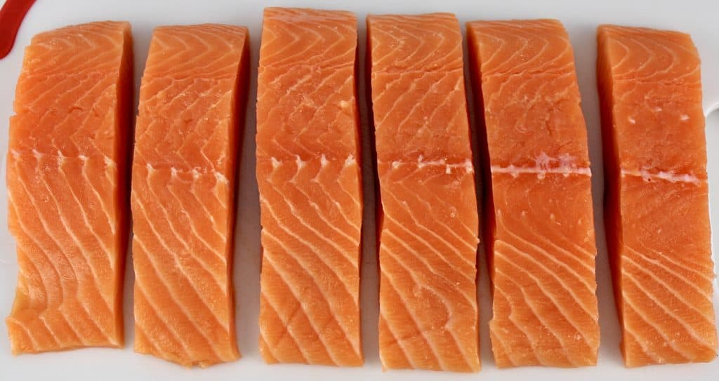 6 pieces of salmon on white cutting board