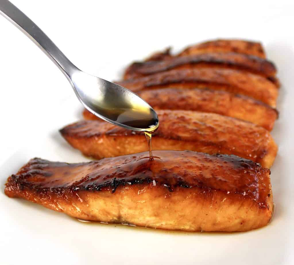 maple syrup being spooned over salmon on white plate