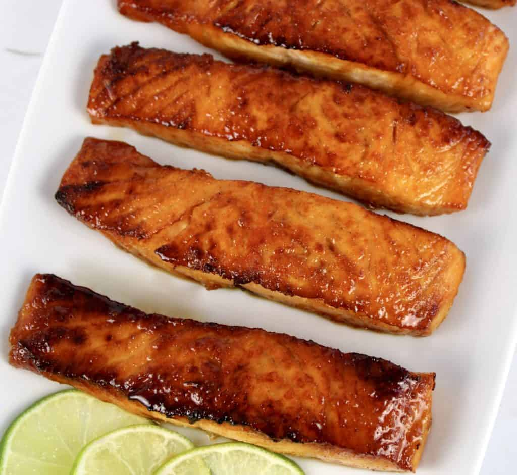 4 pieces of maple glazed salmon on white plate