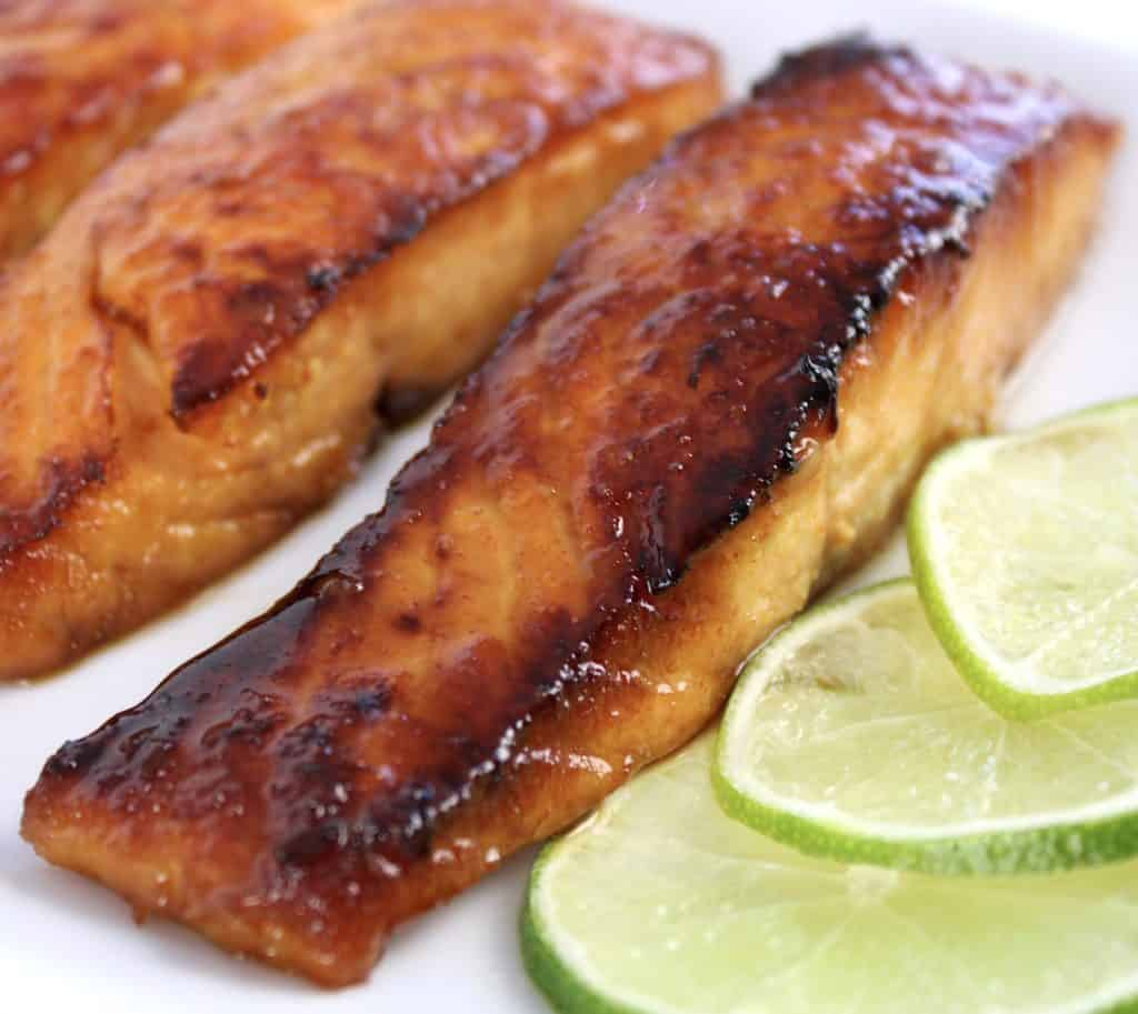 closeup of a piece of maple glazed salmon on white plate with lime slices
