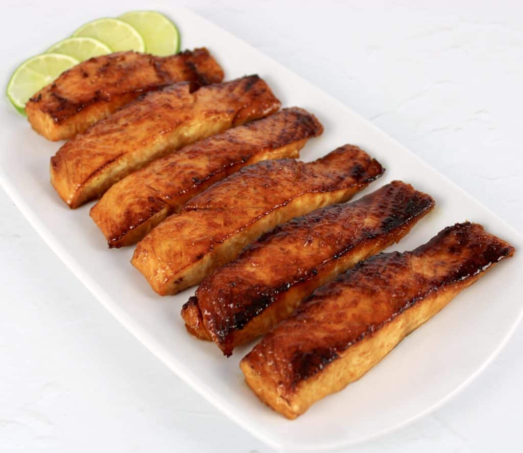 pieces of maple glazed salmon on white plate with lime slices