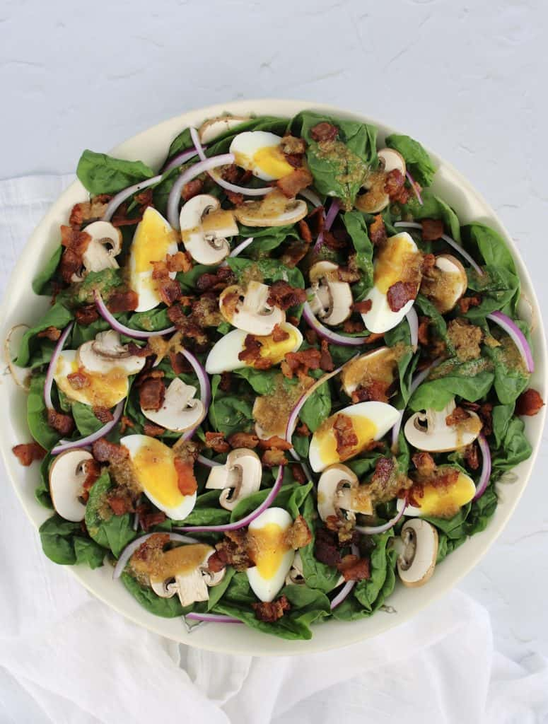 overhead view of spinach salad with hot bacon dressing on top