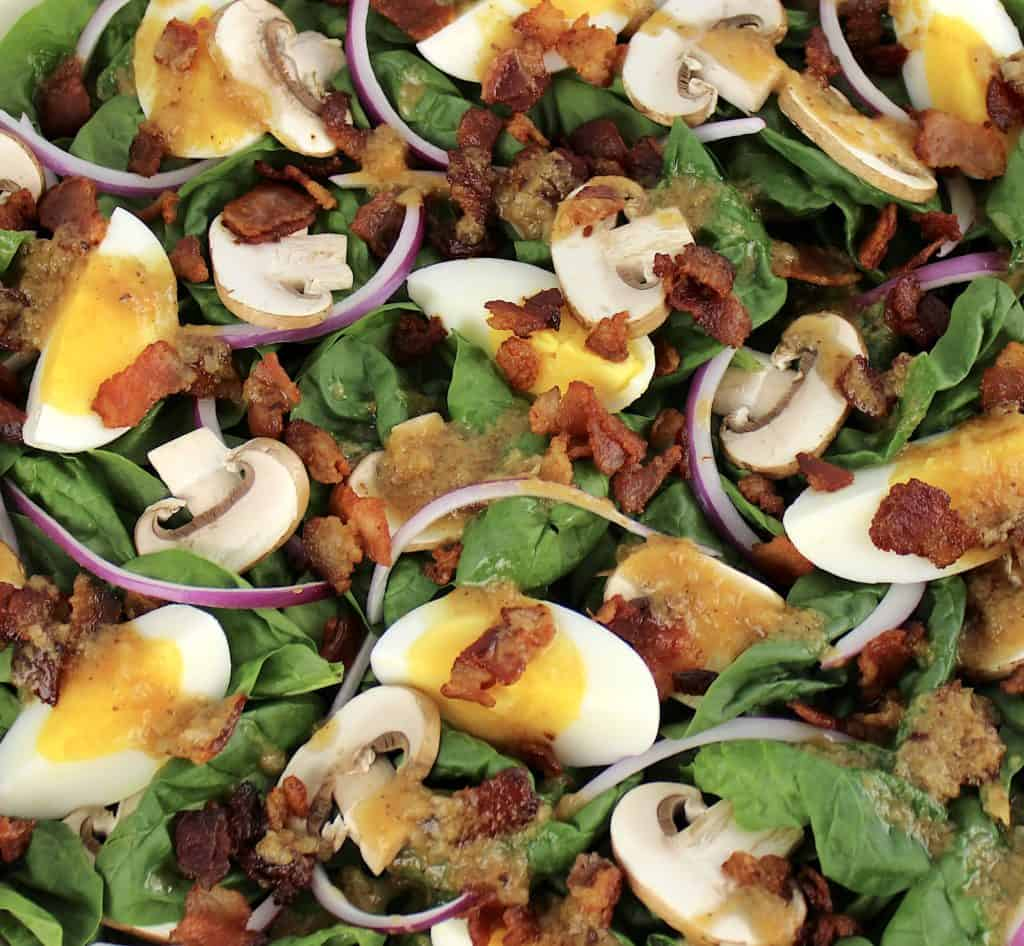 closeup of spinach salad with hot bacon dressing on top