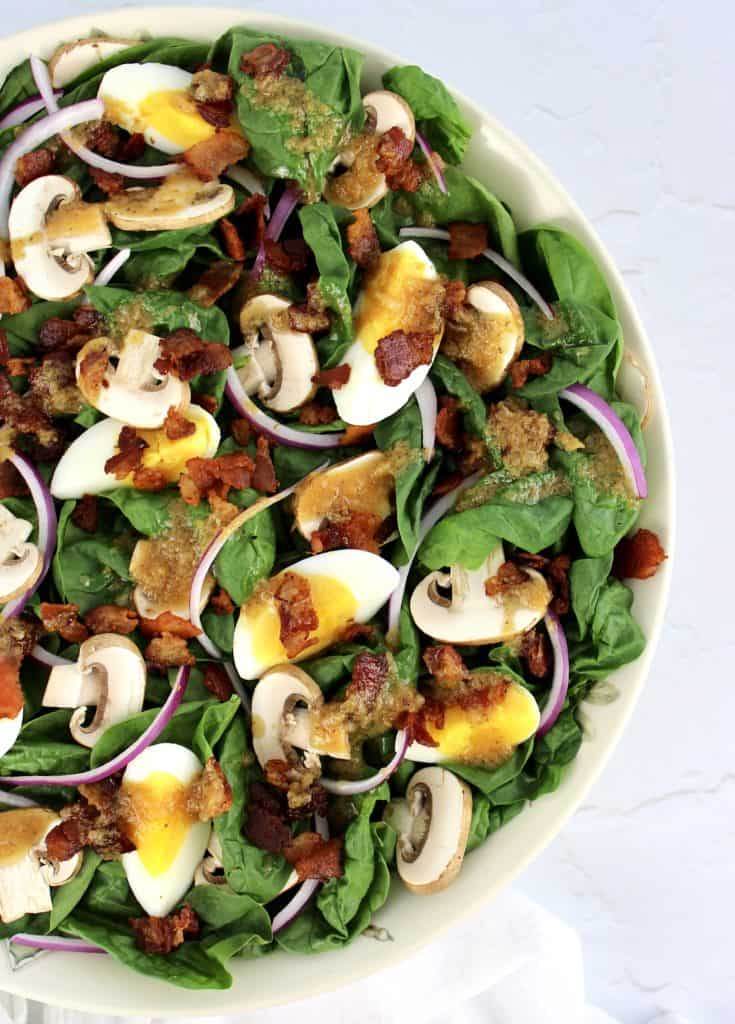 overhead view of Spinach Salad with Hot Bacon Dressing in white bowl