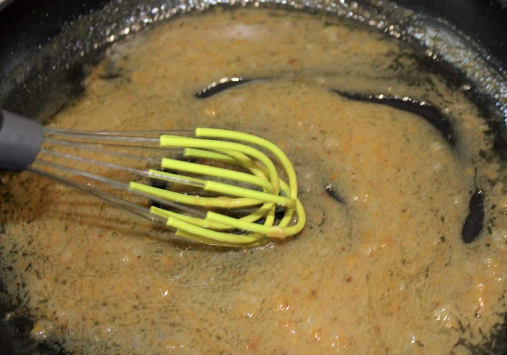 hot bacon dressing in skillet with silicone whisk