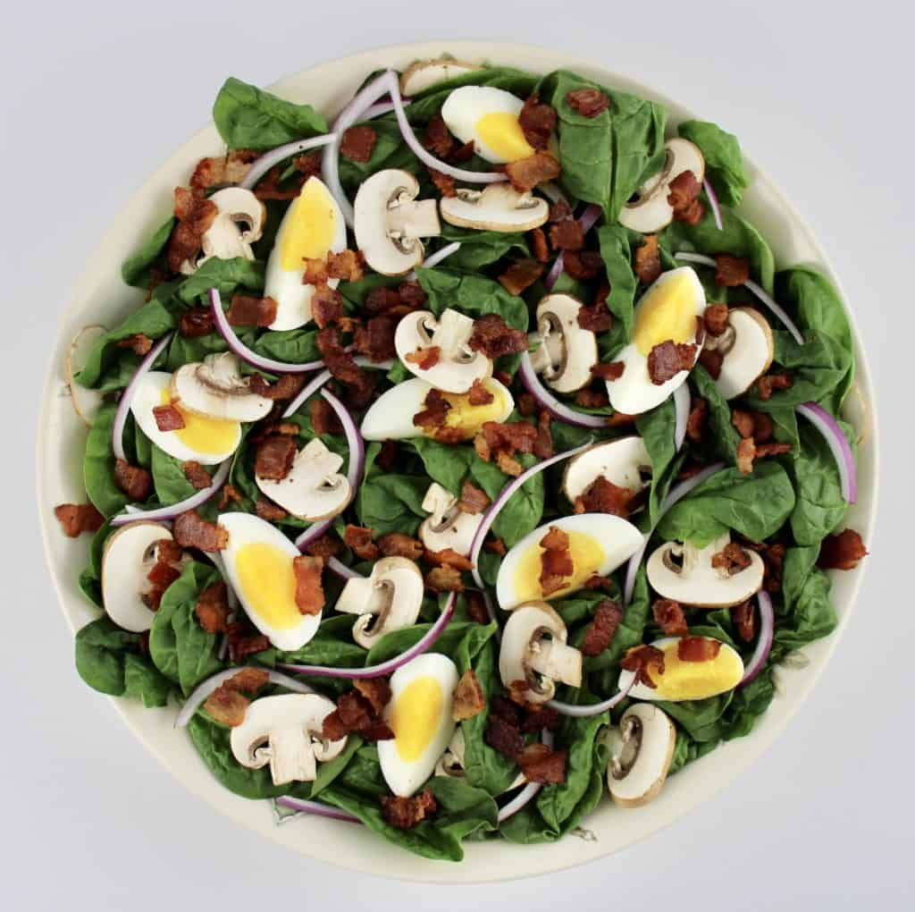 spinach salad without dressing in white bowl