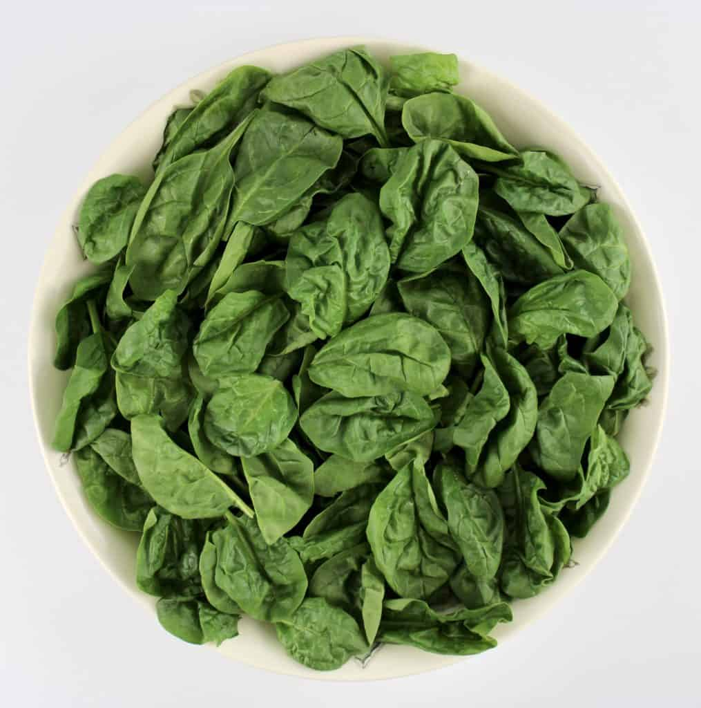 raw spinach in white bowl