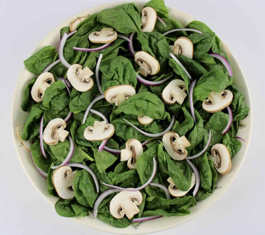 raw spinach sliced mushrooms and red onion in white bowl