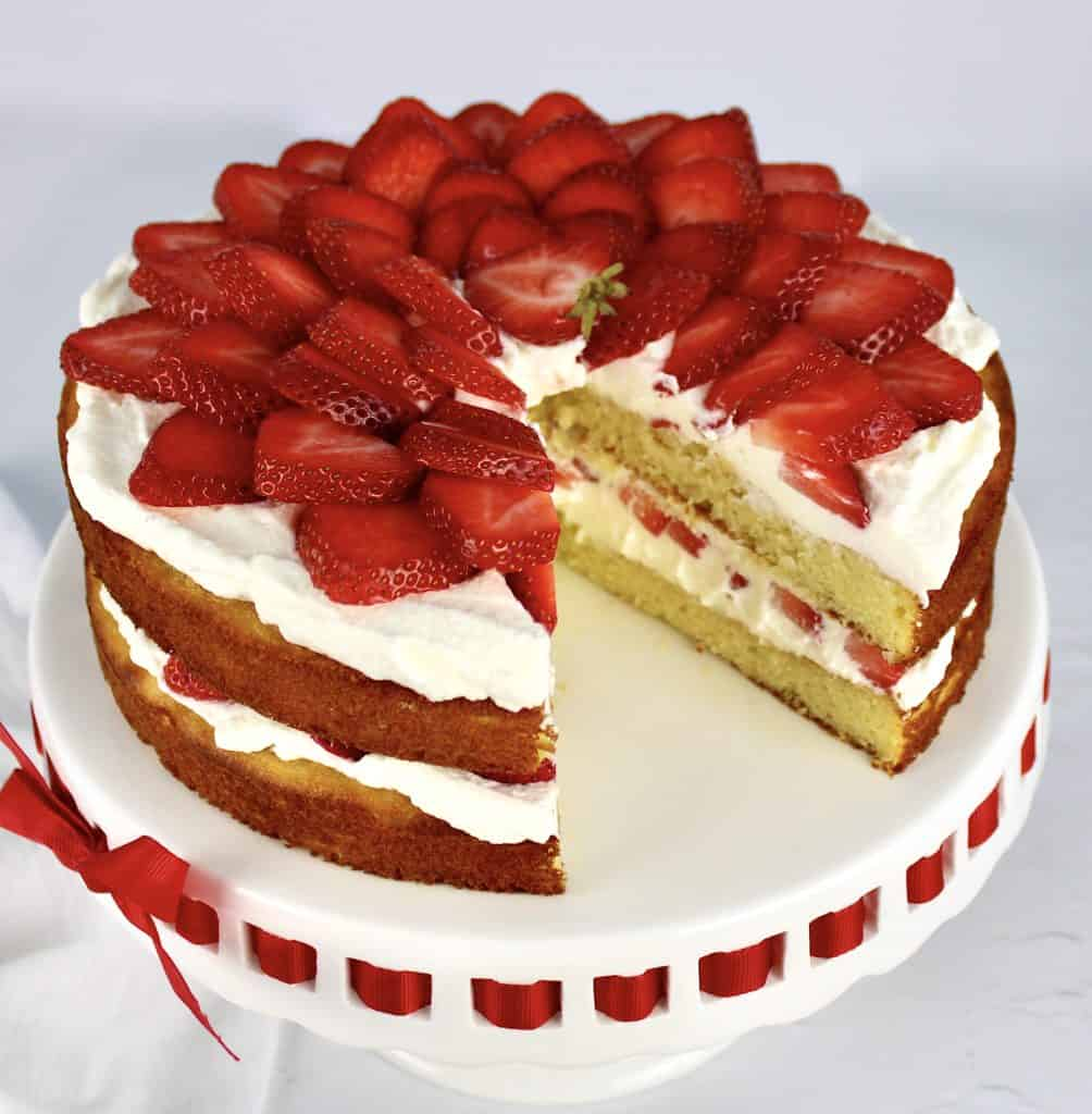 strawberry shortcake on cake stand with slice missing